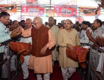 Haryana Chief Minister, Mr. Manohar Lal showering flower petals on people during a function at Sonipat. Member of Parliament, Mr. Ramesh Chander Kaushik is also seen in the picture.